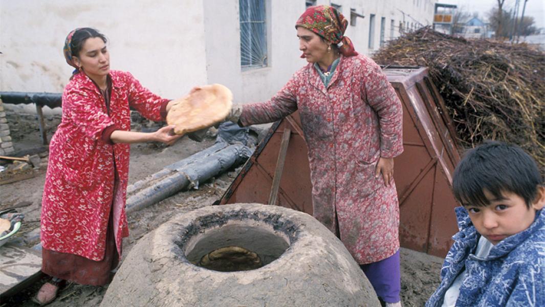 Женщины пекут лепешки в тандыре на улице села Муграб