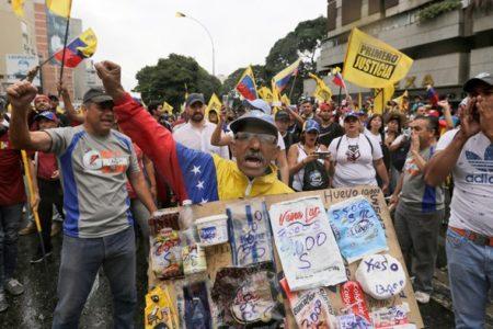 Участник оппозиционнного митинга держит плакат с ценами на продукты. В Венесуэле дефицит продуктов питания и медикаментов. Минимальная зарплата в стране составляет $30 в месяц